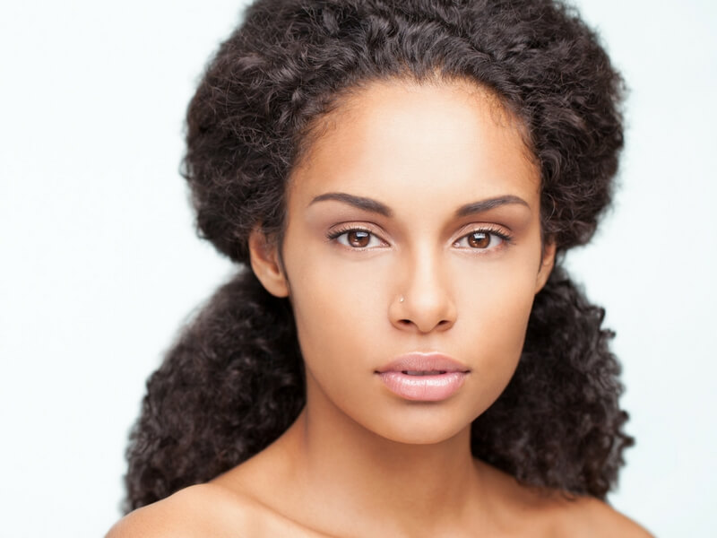 Headshot of African-American women looking serious, without a shirt. Thinking about risks of uterine fibroids.