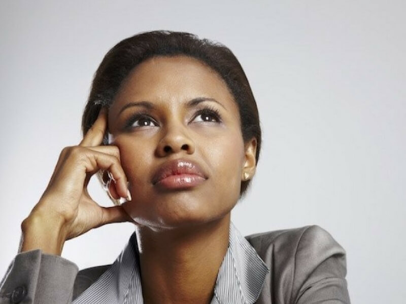 A pensive business women thinking about if Uterine Fibroid Embolization (UFE) is right for her.