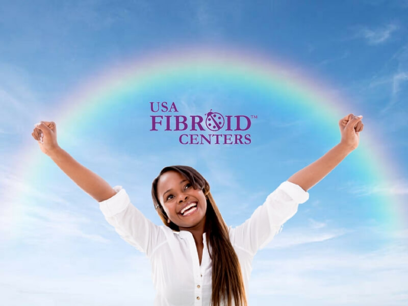 Young Woman smiling, arms outstretched to the sky--a rainbow & the USA Fibroid Centers' logo above.
