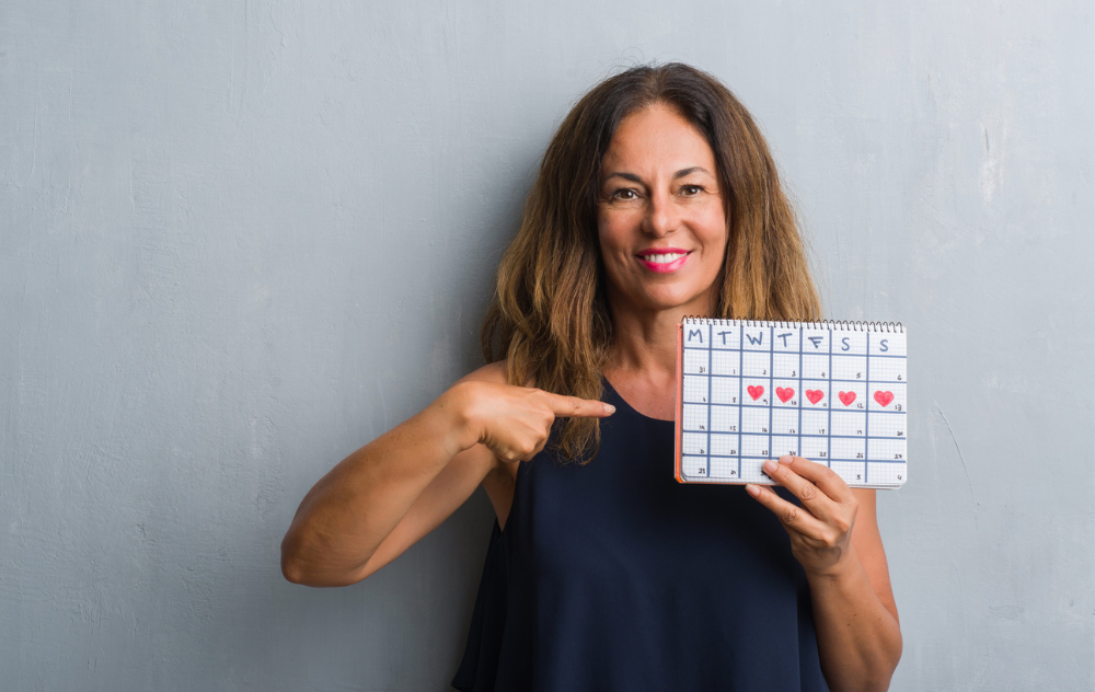 Woman holding a calendar of the menstrual cycle
